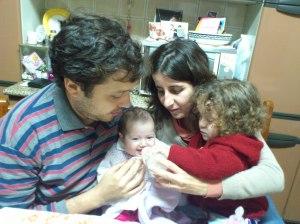 Flávia tomando mamadeira no colo da Maria Teresa, tio Daniel e tia Lidia